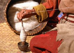 אישה טווה חוטי צמר מצמר גולמי ומלפפת אותם על הכישור